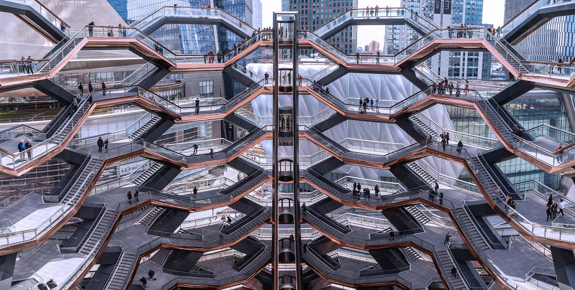 The elevator in the Vessel at Hudson Yards New York City ascends the copper clad spiraling staircases designed by Heatherwick Studios
