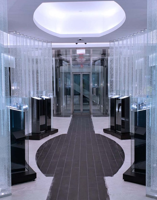 Custom Elevator design with a complete glass enclosure seamlessly integrated into the showroom