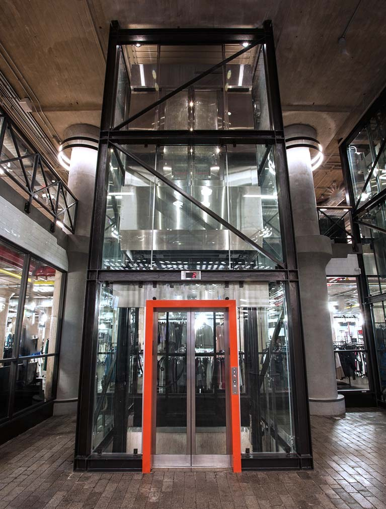 850 Third Ave, Brooklyn, straight on from lobby, glass elevator with black steel girders & orange accent door frame