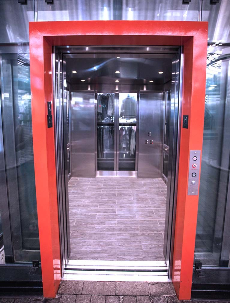 850 Third Ave, Brooklyn, glass elevators with black steel girders & orange accent door frames
