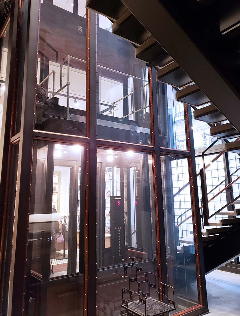 Coach custom glass elevator integrated into the stairway