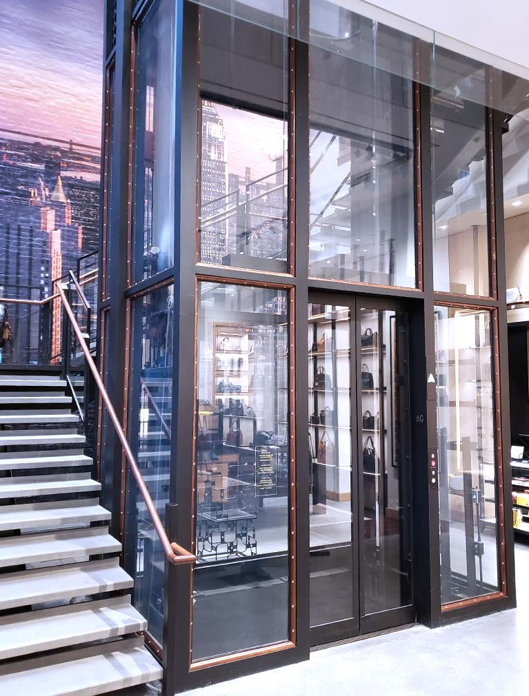 Custom Elevator design integrated into showroom with glass shaft, wood trim and brass rivets