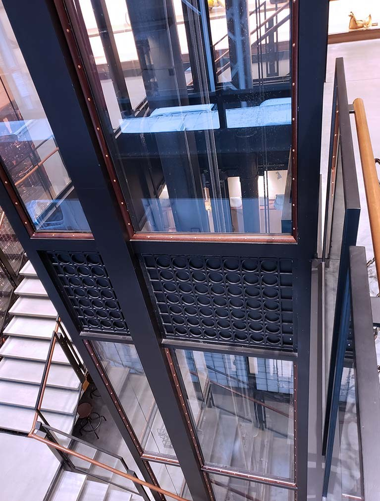 Coach custom elevator shaft of glass and intricate design elements reflect the brand showroom