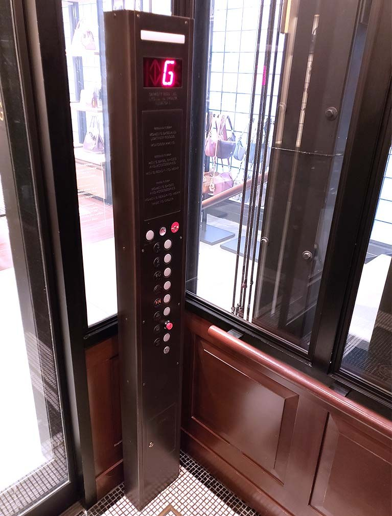 Coach held to brand standards in their pillar designed elevator call buttons