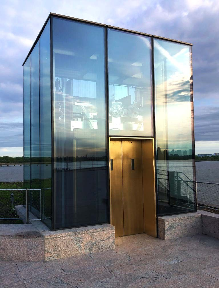 Liberty Island Museum Glass Elevator with copper doors, glass facade and sunrise reflecting in the glass