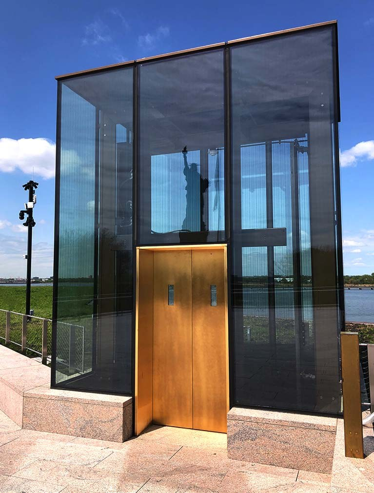 Liberty Island Museum Glass Elevator with copper doors and the reflection of the Statue of Liberty in the glass facade