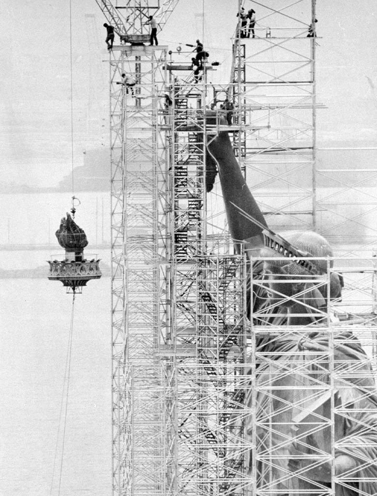 statue of liberty 1986 surrounded by scaffolding while torch is lowered