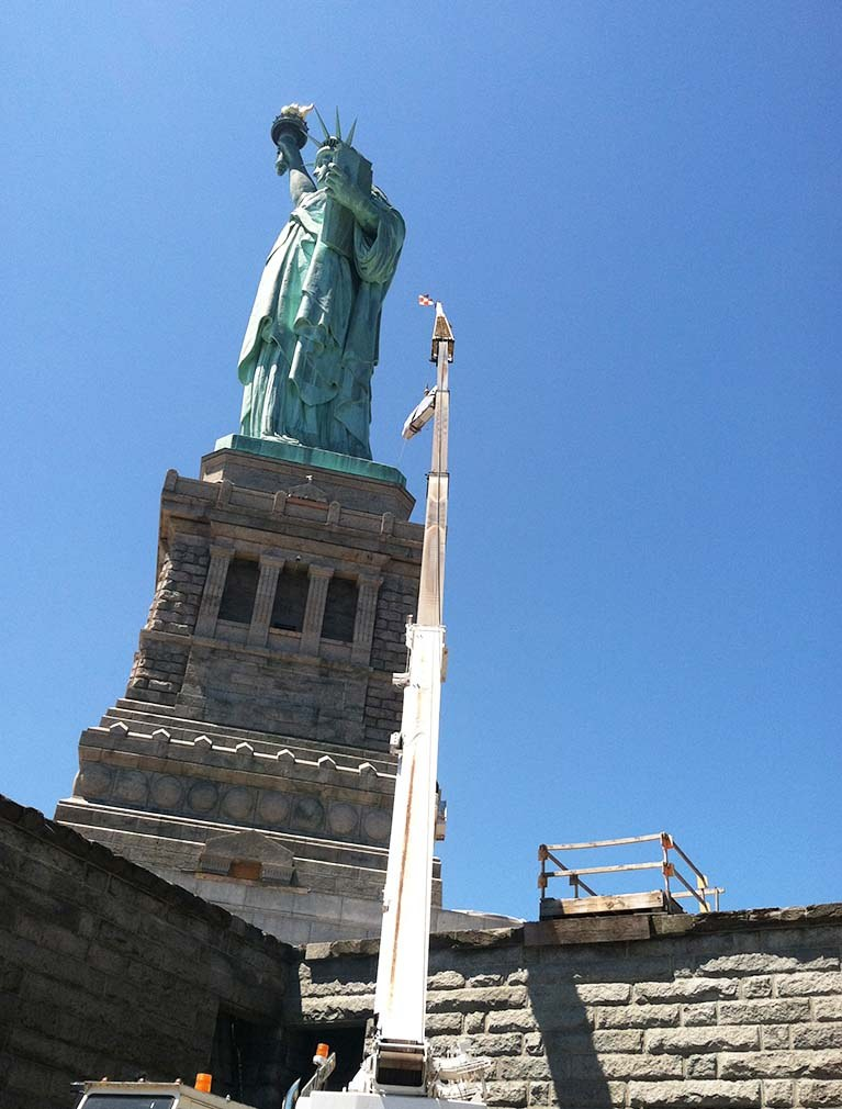 Statue of Liberty 2014 with a crane lifting the elevator motor in place