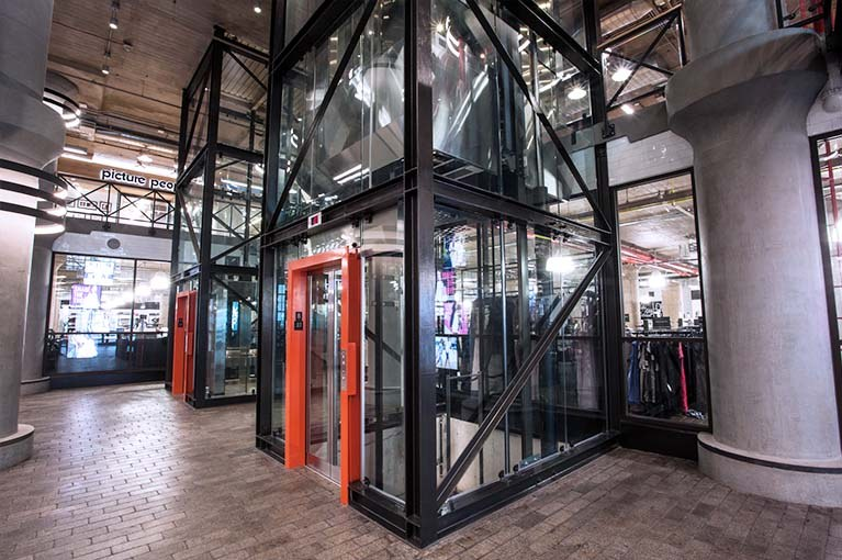 850 Third Ave, Brooklyn, double elevator bay, angle lobby, glass elevators with black steel girders & orange accent door frames