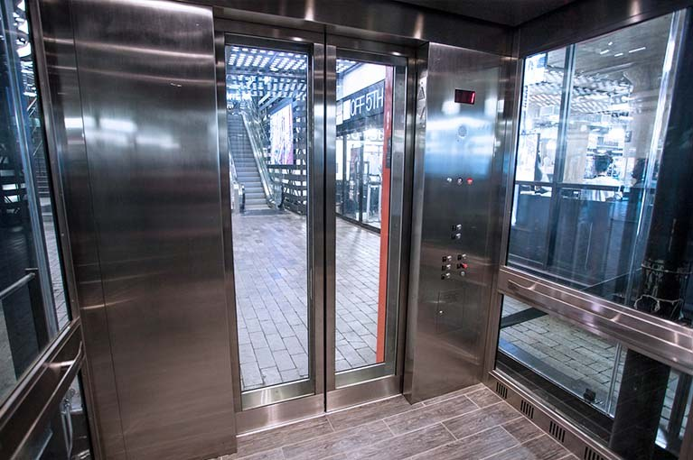 850 Third Ave, Brooklyn, glass elevator cab interior with stainless steel & glass panels