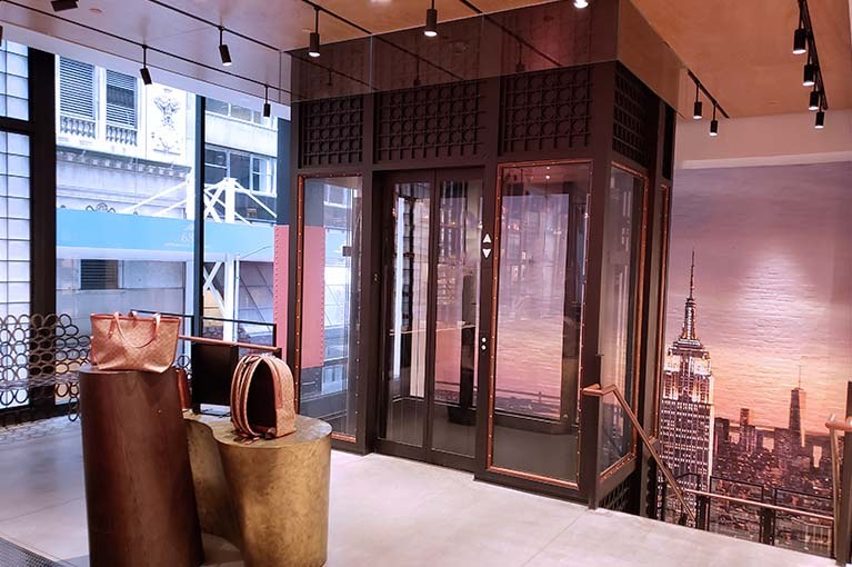 Coach custom glass elevator seamlessly integrates into the showroom with NYC skyline painting behind and handbag displays surrounding
