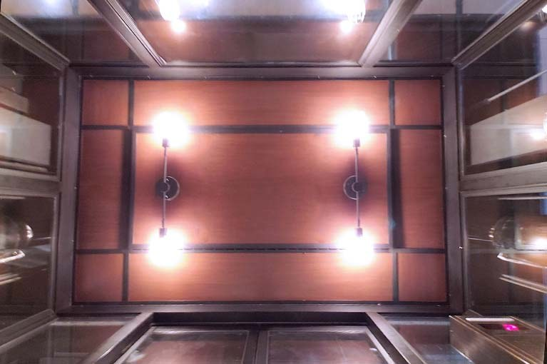 Coach used Edison style bulbs and classic light fixtures to reflect their brand elements into this elevator