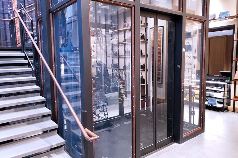 Coach first floor landing of custom glass elevator with wood and brass rivets integrated into the showroom floor