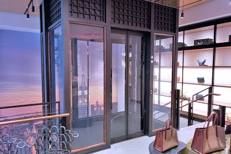 Custom Elevator design with glass shaft, wood trim and seamless integration into the showroom