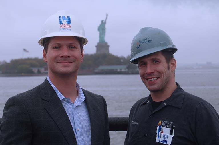 Doug & Darren Muttart of Liberty Elevator with the Statue of Liberty in the background