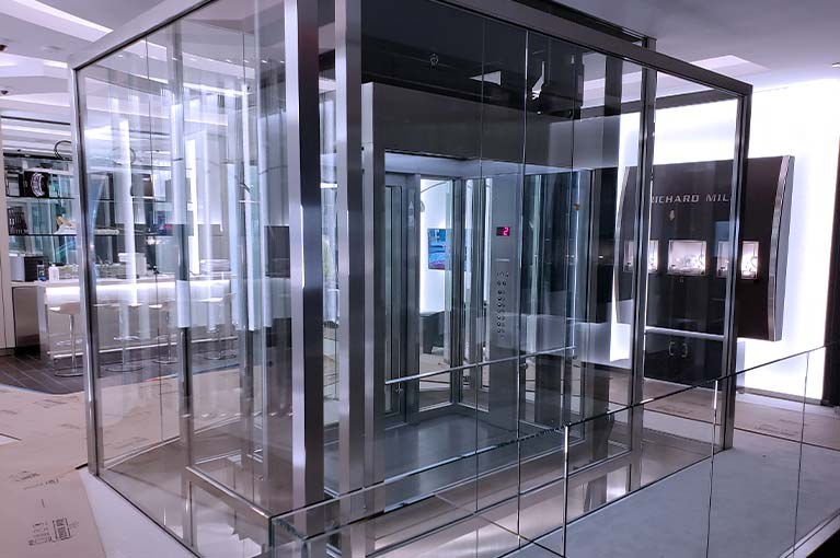 Custom Elevator installation glass and stainless steel with beveled edges