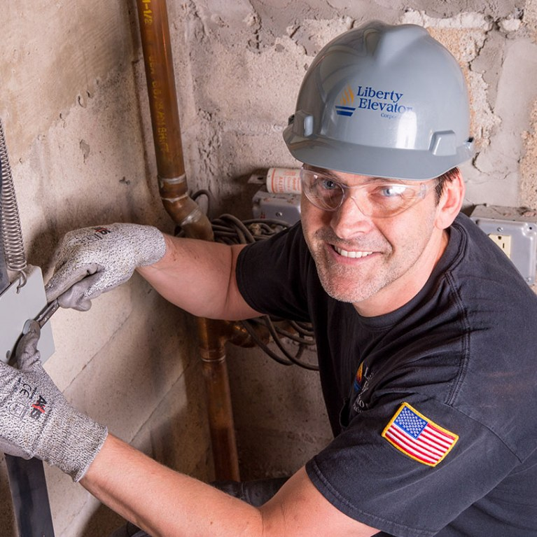 Elevator installation mechanic delivering service with a smile